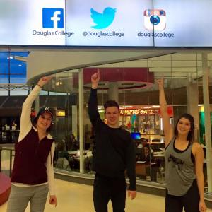 students point at the student life social media handles on the omnivex