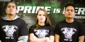 3 students in front of a banner that reads fear the pride, while wearing royals tshirts
