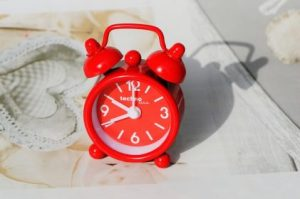 red retro alarm clock sitting on a table