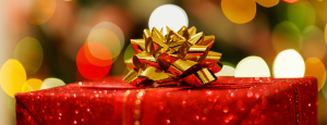 close up of a red christmas present with a gold bow